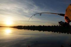 Schattenbild des Spinnens Fischerei bei Sonnenuntergang liebhaberei stockfoto