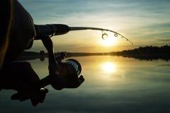 Schattenbild des Spinnens Fischerei bei Sonnenuntergang liebhaberei stockbild