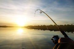 Schattenbild des Spinnens Fischerei bei Sonnenuntergang liebhaberei lizenzfreies stockfoto