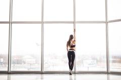 Schattenbild des sportlichen Mädchens vor der Ausbildung gegen panoramische Fenster an der Turnhalle Stockfoto