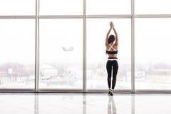 Schattenbild des sportlichen Mädchens vor der Ausbildung gegen panoramische Fenster an der Turnhalle Stockbilder