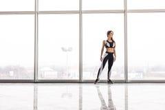 Schattenbild des sportlichen Mädchens vor der Ausbildung gegen panoramische Fenster an der Turnhalle Stockfotos