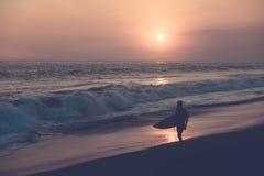 Schattenbild des Surfers gehend am Strand mit Sonnenuntergang lizenzfreie stockbilder