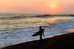 Schattenbild des Surfers gehend am Strand mit Sonnenuntergang lizenzfreies stockfoto
