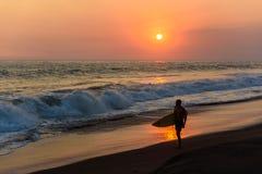Schattenbild des Surfers gehend am Strand mit Sonnenuntergang lizenzfreies stockbild