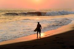 Schattenbild des Surfers gehend am Strand mit Sonnenuntergang stockfotos