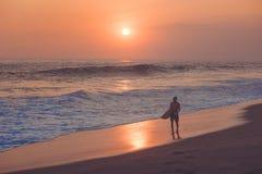 Schattenbild des Surfers gehend am Strand mit Sonnenuntergang stockbilder