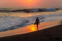 Schattenbild des Surfers gehend am Strand mit Sonnenuntergang stockbild