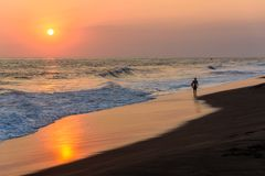 Schattenbild des Surfers gehend am Strand mit Sonnenuntergang lizenzfreie stockfotografie