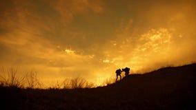 Schattenbild des Teams auf der Spitze des Berges Sport und Berufsleben des Leutemannes und -m?dchens Teamwork-Paarunterst?tzung