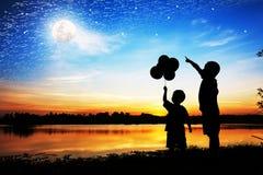 Schattenbild des Vatergebrauchs-Handpunktes sein Sohnblick auf Vollmond Lizenzfreies Stockfoto