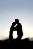 Schattenbild des Vaters Kissing Young Child auf Stirn Lizenzfreie Stockbilder