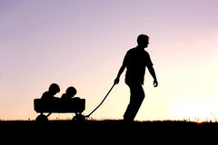 Schattenbild des Vaters Pulling Sons im Lastwagen bei Sonnenuntergang Lizenzfreies Stockbild