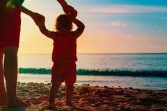 Schattenbild des Vaters und der kleinen Tochter auf Strand Stockbild