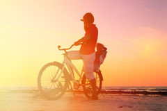Schattenbild des Vaters und des Babys, die bei Sonnenuntergang radfahren Stockbilder