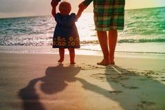 Schattenbild des Vaters und kleine Tochter gehen bei Sonnenuntergang Stockbild