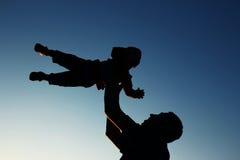 Schattenbild des Vaters und Sohn spielen auf Sonnenuntergang Lizenzfreie Stockfotografie