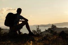 Schattenbild des Wanderers sitzend gegen Himmel Lizenzfreies Stockbild