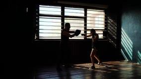 Schattenbild des weißen weiblichen Boxertrainings des Sitzes mit Verpackentrainer an der Turnhalle stock video