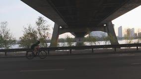 Schattenbild des weiblichen Radfahrerreitfahrrades Seite folgen Schuss Sonnenuntergang in der Stadt mit dem Radfahrer, der Fahrra stock footage