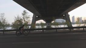 Schattenbild des weiblichen Radfahrerreitfahrrades Seite folgen Schuss Sonnenuntergang in der Stadt mit dem Radfahrer, der Fahrra