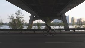 Schattenbild des weiblichen Radfahrers Fahrrad bei Sonnenuntergang unter die Brücke fahrend Film- Radfahrenschuß