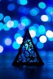 Schattenbild des Weihnachtsbaums mit Verzierung auf blauem bokeh backgro Stockbild