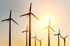 Schattenbild des Windkraftanlagebauernhofes auf Sonnenuntergang lizenzfreie stockfotos