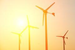 Schattenbild des Windkraftanlagebauernhofes auf Sonnenuntergang stockfoto