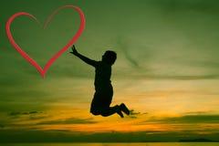Schattenbild durch Kind am Sonnenuntergang und am roten Herzen Stockbilder
