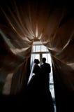 Schattenbild einer Braut und des Bräutigams auf dem Hintergrund von ein Fenster wi Stockbilder