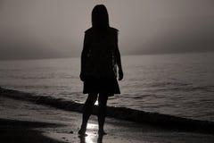 Schattenbild einer Dame, die durch das Meer geht Stockbilder
