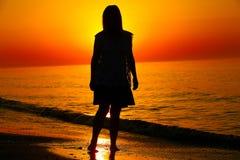 Schattenbild einer Dame, die durch das Meer läuft Stockbilder