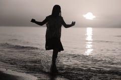 Schattenbild einer Dame, die durch das Meer springt Lizenzfreies Stockfoto