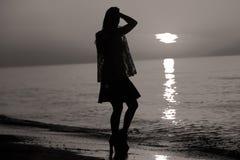 Schattenbild einer Dame, die durch das Meer springt Stockfoto