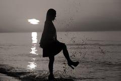 Schattenbild einer Dame, die durch das Meer springt Lizenzfreie Stockfotos