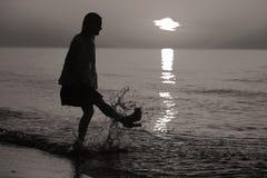 Schattenbild einer Dame, die durch das Meer springt Stockbilder