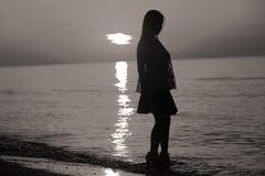 Schattenbild einer Dame, die durch das Meer springt Stockfotos