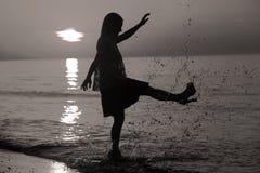 Schattenbild einer Dame, die durch das Meer springt Stockfotografie