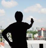 Schattenbild einer in die Seite gestemmten Position des Mannes und einer Hand, die Telefon w halten Stockfoto