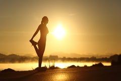 Schattenbild einer Eignungsfrau, die bei Sonnenaufgang ausdehnt Lizenzfreie Stockbilder
