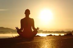 Schattenbild einer Eignungsfrau, die Yogameditation ausübt, trainiert Stockfotografie