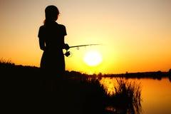 Schattenbild einer Fischenfrau auf der Flussbank auf der Natur an der Dämmerung Lizenzfreie Stockfotos