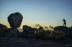 Schattenbild einer Fotografschießensonne, die über den Berg steigt Stockfotografie
