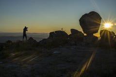Schattenbild einer Fotografschießensonne, die über den Berg steigt Stockfotos