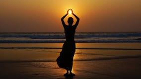 Schattenbild einer Frau auf dem Hintergrund des Sonnenuntergangs. Lizenzfreies Stockbild
