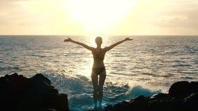 Schattenbild einer Frau bei dem Sonnenuntergang, der Arme in der Luft anhebt und enorme Meereswogen abstürzend auf Felsen und dem stock video footage