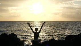 Schattenbild einer Frau, die auf Felsen bei Sonnenuntergang sitzt, Wellen beobachtend und Arme in der Luft anhebend Film- Zeitlup stock video footage