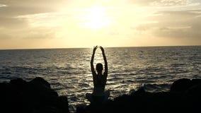 Schattenbild einer Frau, die auf Felsen bei Sonnenuntergang sitzt, Wellen beobachtend und Arme gegen Meereswogen in Film- anheben stock footage