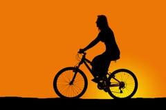 Schattenbild einer Frau, die ein Fahrrad reitet lizenzfreies stockbild